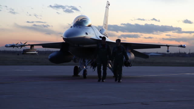 WS F-16 pilots walking away from an F-16 fighter jet at sunset, Aurora, Colorado, USA