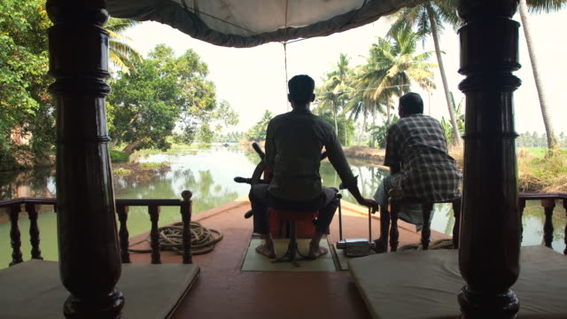 T/L POV Piltot navigating backwaters of Kerala in houseboat / Kollam, Kerala, India
