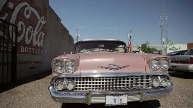 Pink Chevrolet driving slowly towards camera next to Coca Cola mural