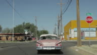Pink Chevrolet driving through streets of Lubbock, Texas