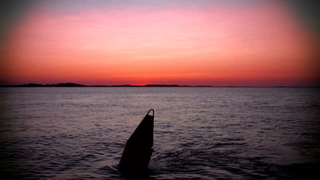 Pink sunset over the ocean, passing a buoy