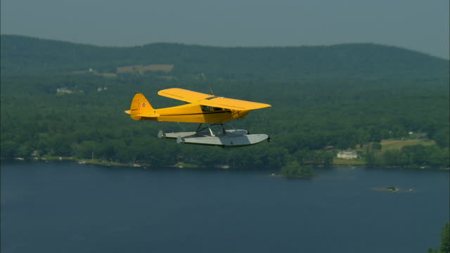 AIR TO AIR, Piper Cub floatplane flying over lake and woods, Megunticook Lake, Maine, USA