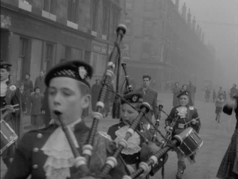 Pipers march down a street in the Gorbals district of Glasgow playing their bagpipes
