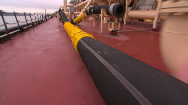 Pipes and tubing occupy the deck of a sludge barge.