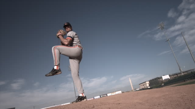 SLO MO LA WS Pitcher winding up and throwing baseball in stadium / Lancaster, California, USA