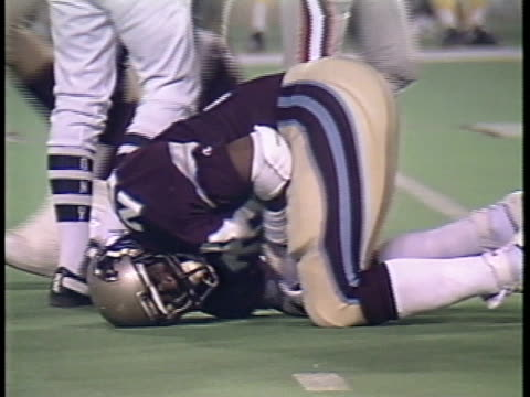 1984 MS Pittsburgh Maulers'  Ernest Adams on ground with Michigan Panthers' Ken Lacy after Lacy was tackled/ MS Lacy writhing in pain with injured arm/ MS Coaches checking on Lacy/ Pontiac, Michigan