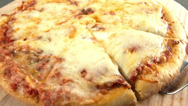 CU pizza slice lifted from freshly baked pizza pulling strings of cheese with it