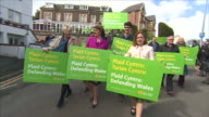 Plaid Cymru leader Leanne Wood walking with supporters holding signs on the general election campaign trail