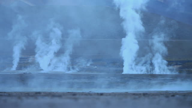 WS Plain with vapour coming out from ground and white van driving then stopping / Geiser del Tatio, Atacama desert, Chile