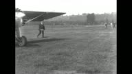 Plane flies low over airport / plane taxis across field / plane comes to stop three men approach door of cockpit policeman standing in foreground /...