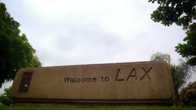 Plane flies over Welcome to LAX sign