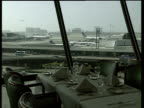 Plane taking off and moving traffic seen through large restaurant windows with set table in foreground LAX Airport