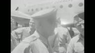 Plane taxiing at unspecified airfield / officer comes down steps from plane greeted by two officers / CU arriving officer / group of officers coming...