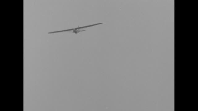 LS plane tows Capt Frank Hawks' glider in air during trip from west coast of US to east coast / people in tree and on ground at Van Cortlandt Park in...