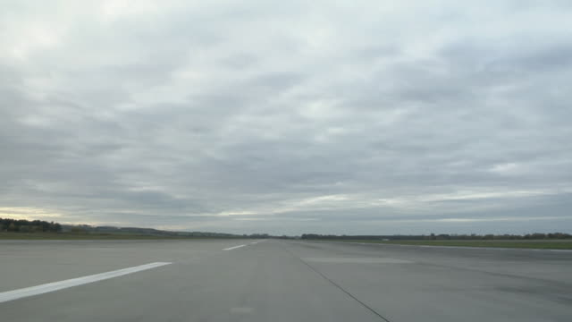 WS POV Plane traveling on runway in remote area surrounded by fields / Brandenburg, Germany