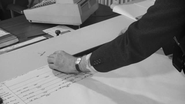 1969 MONTAGE Planning engineer plotting a coal mine network diagram in an office setting / United Kingdom
