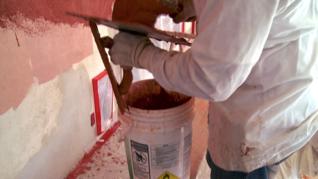 MS Plasterer using bucket trowel to scoop out colored plaster from bucket / Rancho Mirage, California, USA.