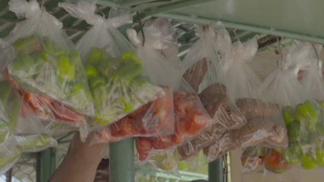 Plastic bags filled with red and green peppers and sweet potatoes hanging