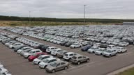 Plastic covers protect the bodywork of new Audi AG SUV automobiles and Volkswagen AG vans awaiting shipping in a parking lot at the Volkswagen Group...