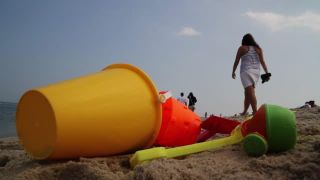 A plastic pail and shovels litter a sandy beach.