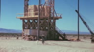 Platform constructed for the pretest calibration explosion with mobile crane to one side and 108 tons of TNT spiked with fission products stacked in...
