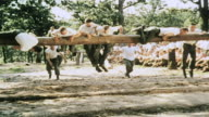 WS Platoon of recruits mounting and passing high obstacle on training course / Fort Leonard Wood Missouri United States