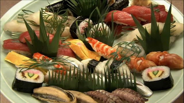 A platter contains an arrangement of sushi items.