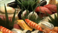 A platter contains an arrangement of sushi items.