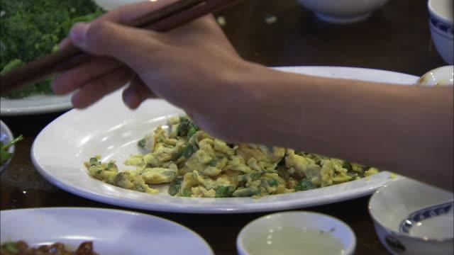 CU Platter of fried eggs being eaten, Beijing, China