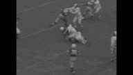 Player makes it for 7 yards during football game between Yale and Cornell / marching band 'Y' on field / crowd / Cornell fumbles Yale recovers /...