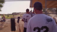 Player number 22 runs to bench at a men's league softball game.