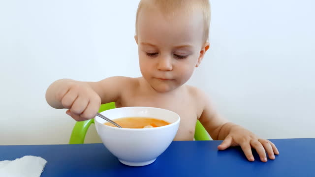 Playful child trying to eat a soup