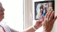 Playful elder couple having fun taking selfies on a tablet with teamwork