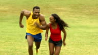 Playful Male and Female Athletes Run Up Hill