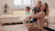 Playful mother having fun with her children at home.