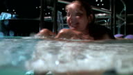 Playful woman enjoying in a wellness pool; underwater camera
