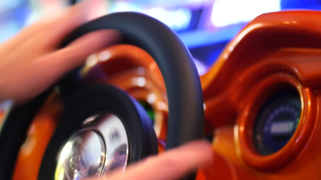 Playing Driving Arcade Video Game - Player Using Steering Wheel Controller - Close Up