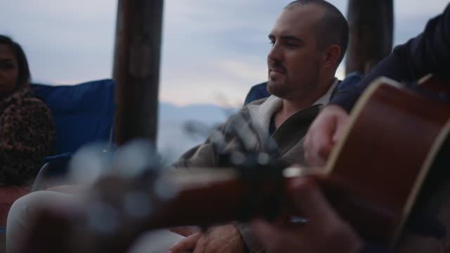 Playing Guitar around campfire
