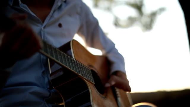 Spielt Gitarre in Natur