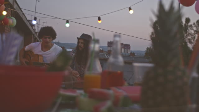 Playing guitar with friend on rooftop party