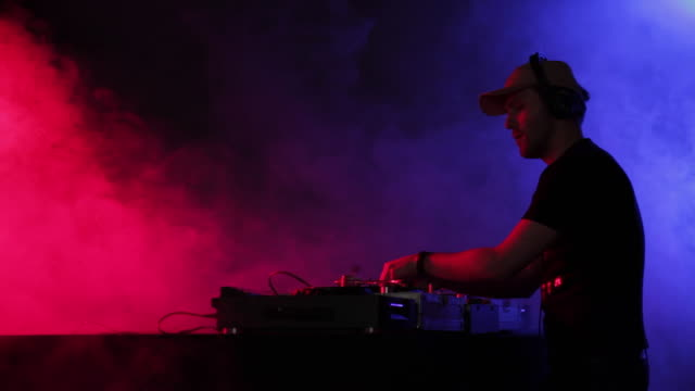 MS DJ playing music, standing at turntables in nightclub / London, United Kingdom