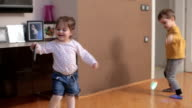 Playing song on mobile phone and dancing in living room