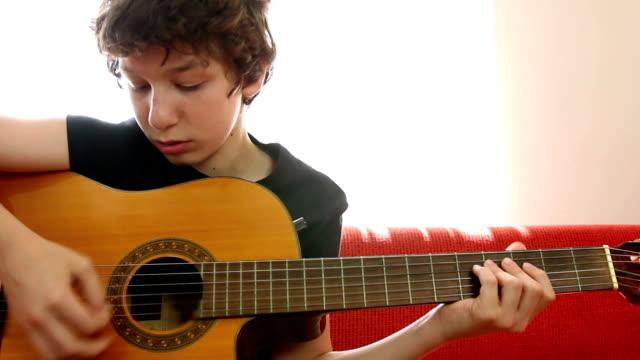 Spielt Gitarre und Haltestellen und blickt in die Kamera.