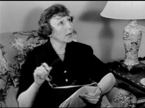 Playwright novelist Rose Franken sitting on couch reading radio script for 'Claudia' radio adaptation CU Radio script page