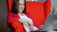 Pleased businesswoman using laptop in an armchair