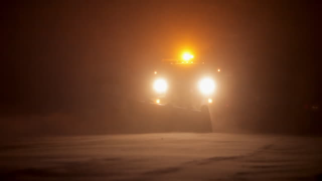 A plow with his lights, scraping the snow in a dark evening