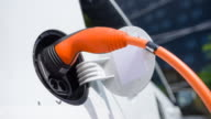 Plugging power cable into electric car to charge batteries in front of office