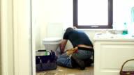 HD DOLLY: Plumber / Handyman fixing the Toilet in Bathroom