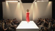 WS Plus-size woman modeling red gown on catwalk while audience watches / London, England, UK