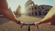 Point of view POV bicycle to the Coliseum of Rome